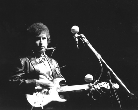 Bob Dylan plays a Fender Stratocaster electric guitar for the first time on stage as he performs at the Newport Folk Festival on July 25, 1965 in Newport, R.I. Photo by Alice Ochs/ Michael Ochs Archives/ Getty Images.