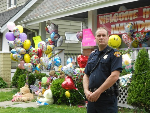 police officer stands watch outside the family home of Amanda Berry ...