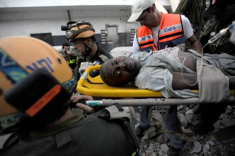 Israeli workers carry a man from a collapsed building in Port-au-Prince. Photo: Juan Barreto/AFP/Getty Images