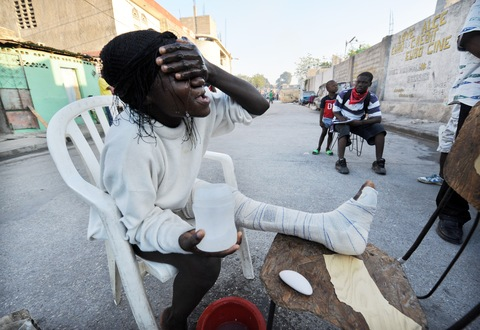 A Haitian earthquake victim washes her face at a shelter in Port-au-Prince. Photo Credit: Jewel Samad/AFP/Getty Images