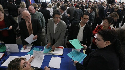 Job seekers speak to recruiters in San Mateo, Calif. Justin Sullivan/Getty Images