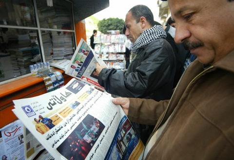 Kurdish Iraqi men read newspapers