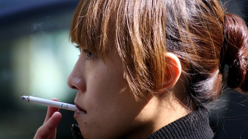 Young woman smoking; Photo credit: Flickr user Tadolo