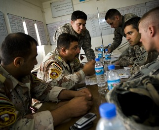 An Iraqi Army officer talks to US soldiers during an exchange of intelligence at an Iraqi Army base on June 2, south of Mosul, Iraq. Photo by Warrick Page/Getty Images