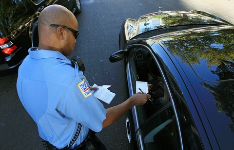 Officer Tyrone Gross hands out a warning to a motorist who was talking on his cell phone on Sept. 21 in Washington, D.C. Photo by Mark Wilson/Getty Images