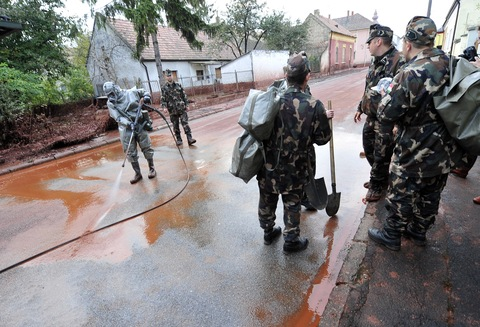 Soldier wearing a chemical protection outfit cleans a street of Devecser