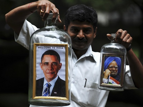 Indian artist Basavaraju Gowda holds bottles containing framed portraits of President Barack Obama and Indian Prime Minister Manmohan Singh in Bangalore. DIBYANGSHU SARKAR/AFP/Getty Images