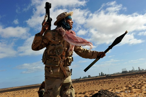 A Libyan rebel fighter holds a rocket propelled grenade (RPG) launcher after spotting a fighter jet flying overhead near a checkpoint at the entrance to the oil rich town of Ras Lanuf on March 6, 2011.  (ROBERTO SCHMIDT/AFP/Getty Images)