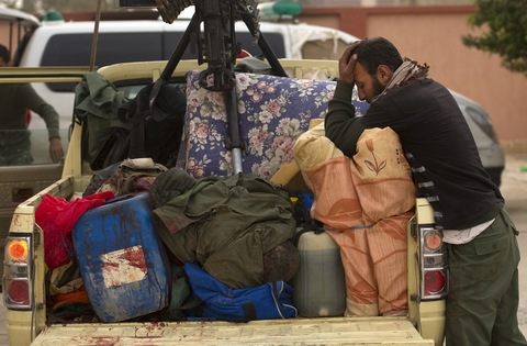 A Libyan rebel fighter mourns over a fallen comrade whose body lies in the back of their fighting vehicle as they arrive at a mortuary in Ajdabiya on April 7, 2011. (Odd Andersen/AFP/Getty Images)