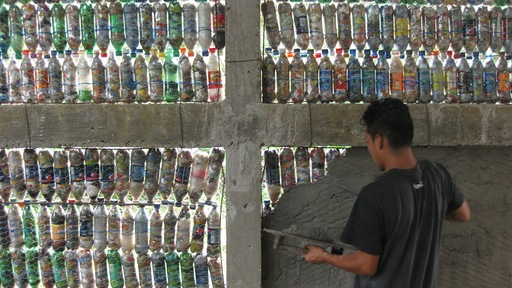 A volunteer applies the first layer of cement to the encased bottles.