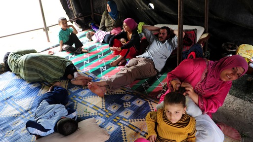 Syrian internally displaced persons rest at a makeshift camp. Photo by Mustafa Ozer/AFP/Getty Images