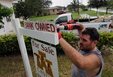 Renzo Salazar places a sign in front of a foreclosed home on Oct. 13 in Miami, Florida; Photo by Joe Raedle/Getty Images