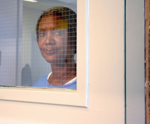 Debbie Peagler stands behind security glass at the Central California Women's Facility Prison in Chowchilla, CA.