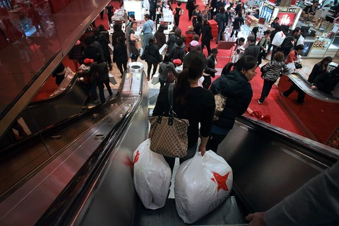 Customers ride down an escalator with shopping bags at a Macy's Inc. store in New York.