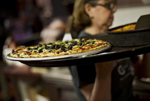 A waitress carries a pizza to customers at Gino's East restaurant in Chicago