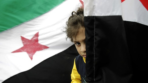 A child stands behind a Syrian flag. Photo by Joseph Eid/AFP/Getty Images.