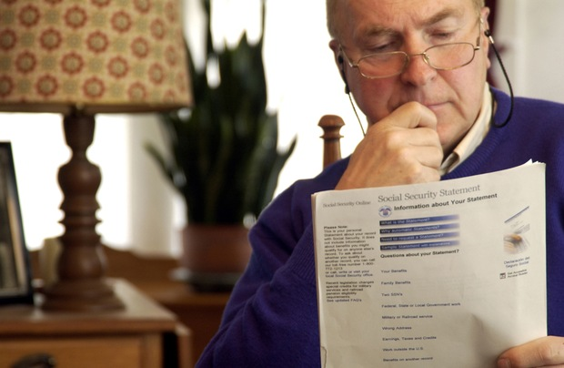 A man examines his Social Security paperwork.