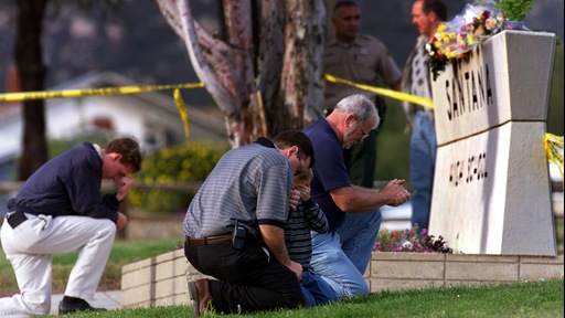 Residents of Santee California pray on the Santana High School grass after dropping flowers in remembrance of the two students killed and 13 wounded by Andy Williams in 2001.  Photo by Gina Ferazzi