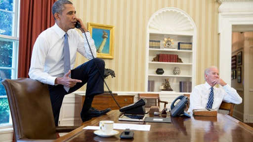 President Obama talks on the phone with Speaker of the House Boehner as Vice President Biden listens in the Oval Office of the White House August 31, 2013 in Washington, DC.